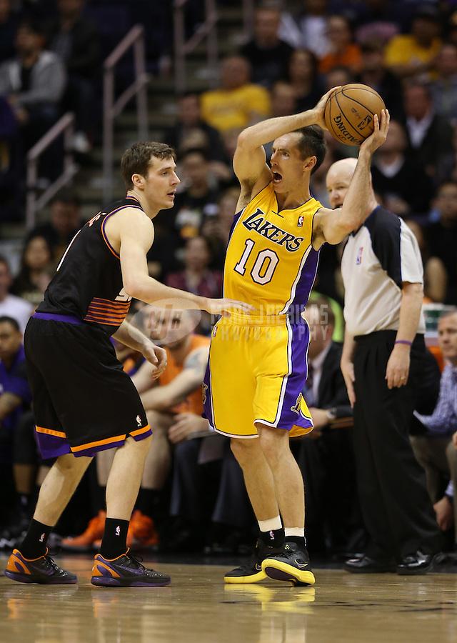 Jan. 30, 2013; Phoenix, AZ, USA: Los Angeles Lakers guard Steve Nash (10) controls the ball against Phoenix Suns guard Goran Dragic at the US Airways Center. Mandatory Credit: Mark J. Rebilas-