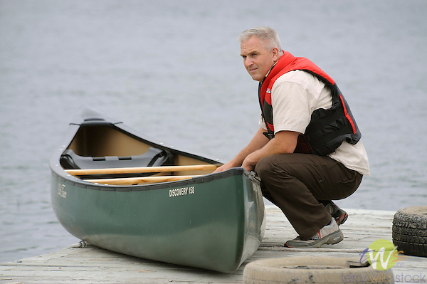 International Seaplne Fly-In. Moosehead Lake. Bush pilot canoe race. Man on dock with canoe before competition.