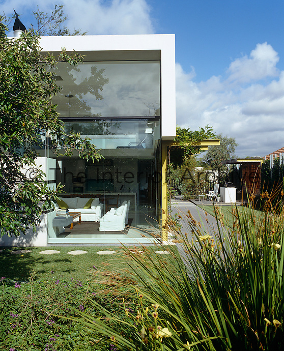 The double-height picture windows in the open-plan living area look out onto the lush  garden