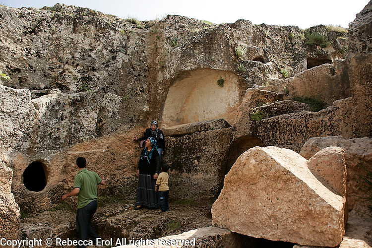Turkish family exploring the rock-cut tombs of the ancient city of Perre near Adiyaman, Turkey