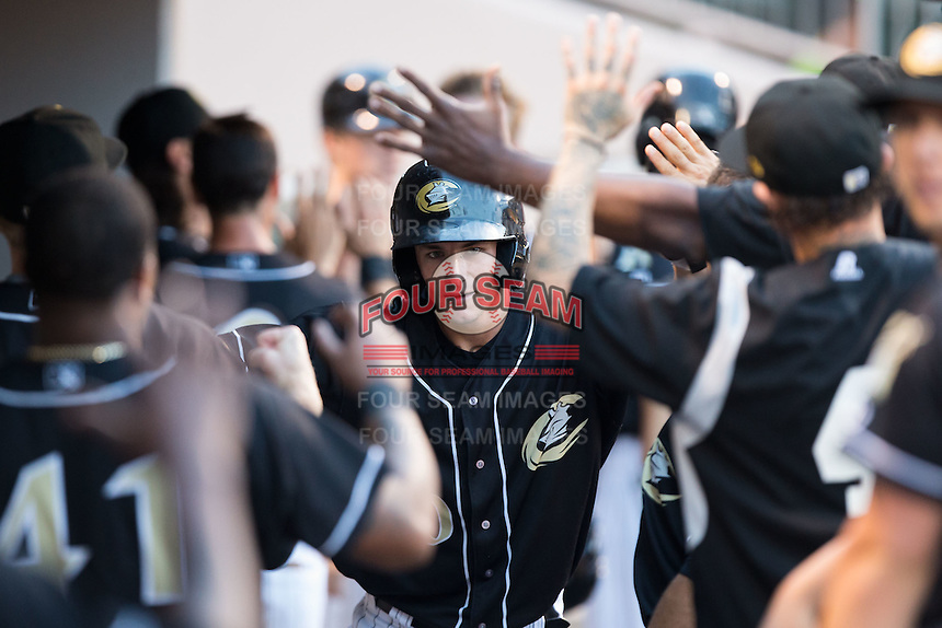 Rob Brantly (20) of the Charlotte Knights is congratulated by his teammate after hitting a home run against the Gwinnett Braves at BB&T BallPark on August 11, 2015 in Charlotte, North Carolina.  The Knights defeated the Braves 3-2.  (Brian Westerholt/Four Seam Images)