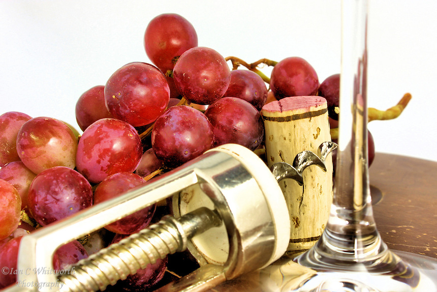 View of grapes,wine glass stem, cork and screw.