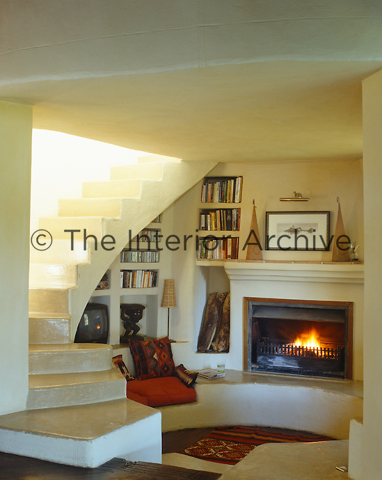 Books and videos are stored on shelves beneath the curve of the staircase at the fireplace end of the living room