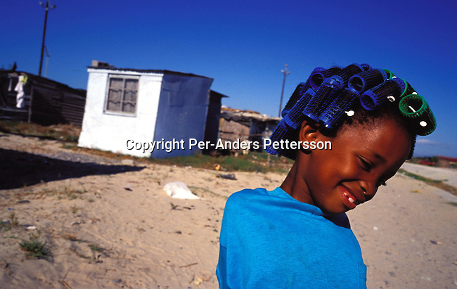 ditown00190 Digital. Township A young girl with colorful spools (curlers) in her head on August 11, 2001 in the Site Mufuleni section in Khayelitsha, a township about 35 kilometers outside Cape Town, South Africa. Khayelitsha is one of the poorest and fastest growing townships in South Africa. People usually come from the rural areas in Eastern Cape province to find work as maids and laborers. Most people don't find work and the unemployment rate is very high, together with lot of violence and a growing HIV-Aids epidemic itÕs a harsh area to live in..©Per-Anders Pettersson/iAfrika Photos..
