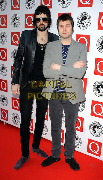 KASABIAN - Serge Pizzorno & Tom Meighan .The Q Awards 2010, Grosvenor House Hotel, Park Lane, London, England, UK..October 25th, 2010.full length black jacket grey gray leather sunglasses shades arms crossed jeans denim blue striped stripes .CAP/WIZ.© Wizard/Capital Pictures.