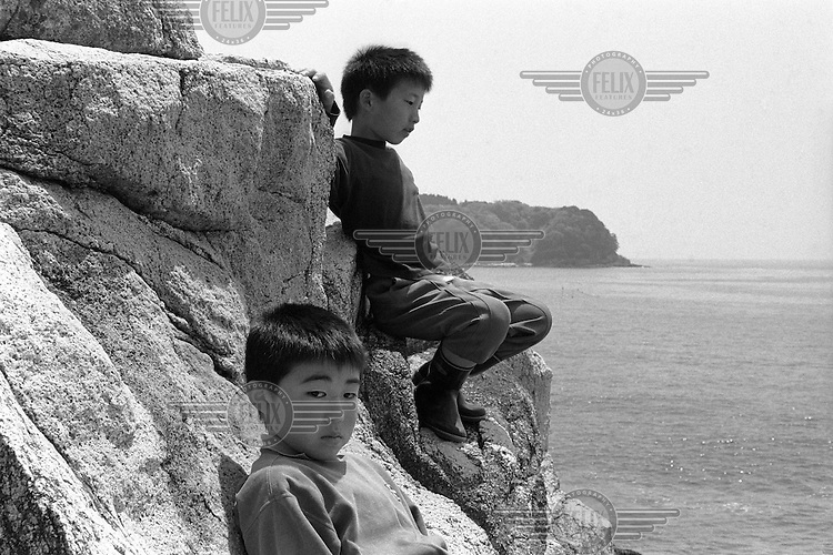 Schoolboy friends lookout over the Pacific Ocean from a viewpoint behind Tennohama Village, Yamada Township, Iwate Prefecture.