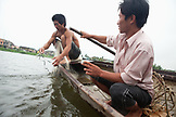 VIETNAM, Hue, Perfume river, fisherman Tran Van Son with his casting net and driver Tran Van Luong in their Sampan boat, La Y Village, Phu Vang District, Thua Thien Hue Province