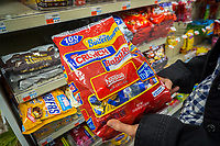A shopper chooses a bag of Nestlé's brand chocolate candy in a store in New York on Thursday, June 15, 2017. Because of a sluggish demand for chocolate Nestlé is considering selling its U.S. chocolate business. (© Richard B. Levine)