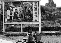 A boy passes a sign in Huaji county in north Guangdong close to Guanxi that reads 'fewer children, better life' . The Chinese country-side has is often the target of the Birth Control Units who use excessive force to keep the population down.