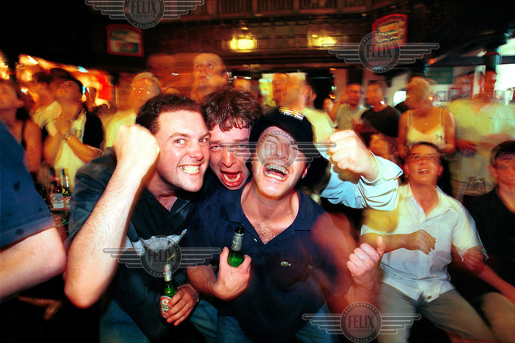 Football supporters celebrate while watching an England match in the Euro 2000 football tournament in the Friary and Firkin pub.