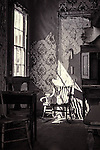 Infrared image of old rocking chair with sun shining through window and torn wall paper