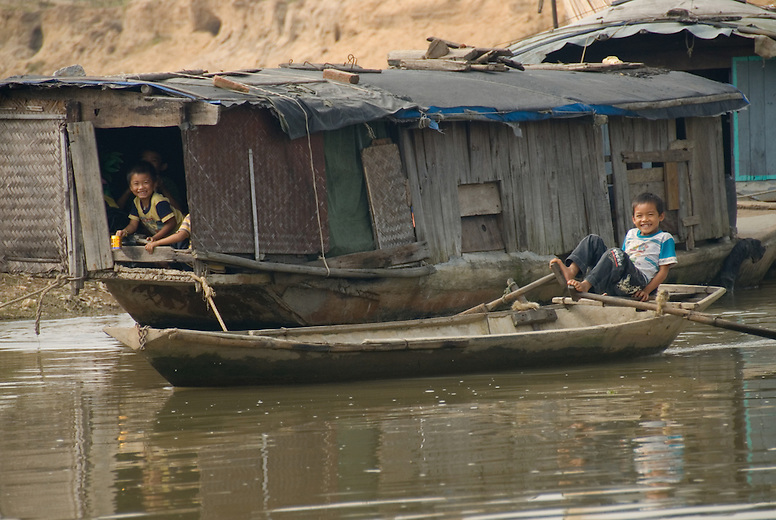 Young boys play in their houseboat along the river in a small village just outside of Hanoi, Vietnam