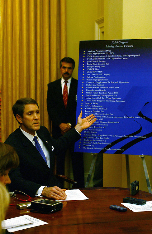 "11/25/03.FRIST/108TH CONGRESS--Senate Majority Leader Bill Frist, R-Tenn., during a pen and pad briefing in his office after final passage of Medicare. Behind him is a poster entitled, ""108th Congress Moving America Forward,"" listing legislation passed in the session..CONGRESSIONAL QUARTERLY PHOTO BY SCOTT J. FERRELL"