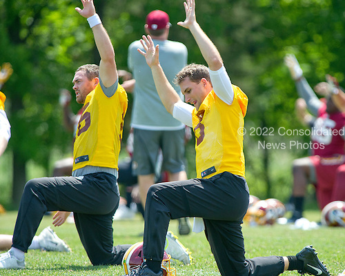 Washington Redskins quarterbacks Colt McCoy (16), left, and Kirk Cousins (8), right, participate in warm-up drills during an organized team activity (OTA) at Redskins Park in Ashburn, Virginia on Wednesday, May 25, 2015.<br /> Credit: Ron Sachs / CNP