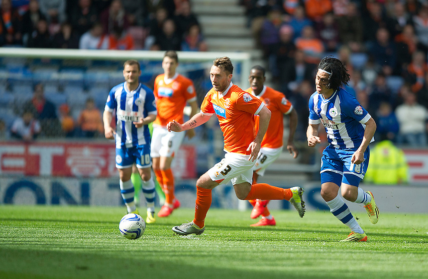 Blackpool's Stephen Dobbie chased by Wigan Athletic's Roger Espinoza<br /> <br /> Photo by Stephen White/CameraSport<br /> <br /> Football - The Football League Sky Bet Championship - Wigan Athletic v Blackpool - Saturday 26th April 2014 - DW stadium - Wigan<br /> <br /> &copy; CameraSport - 43 Linden Ave. Countesthorpe. Leicester. England. LE8 5PG - Tel: +44 (0) 116 277 4147 - admin@camerasport.com - www.camerasport.com