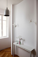 In the master bedroom an elegant console table sits in front of a partition painted a chalky white