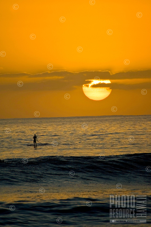 Paddle-surfer watches the sun set as he waits for one more wave at Makaha Beach on the Leeward side of Oahu, Hawaii.