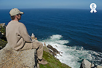 Man sitting on rock by sea, rear view (Licence this image exclusively with Getty: http://www.gettyimages.com/detail/73014013 )