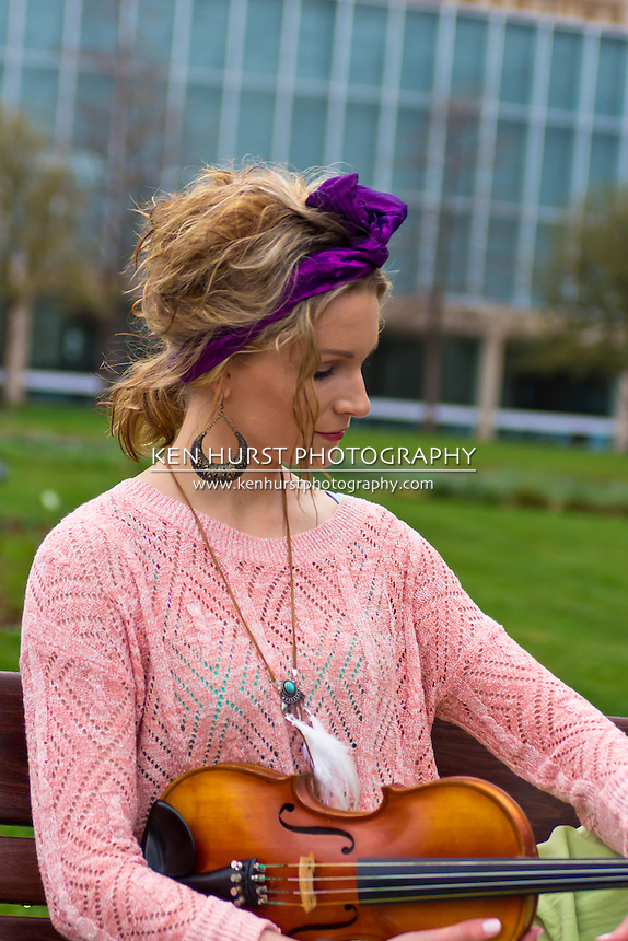 Portrait of a beautiful Bohemian woman with colorful clothes holding a violin.