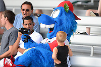 Williamsport Crosscutters mascot Boomer borrows a radar gun as a young fan asks questions during a game against the Auburn Doubledays on July 8, 2013 at Bowman Field in Williamsport, Pennsylvania.  Auburn defeated Williamsport 5-1.  (Mike Janes/Four Seam Images)