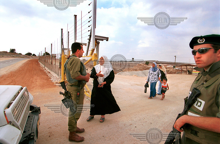 A Palestinian woman asks for a permit to enter the West Bank city of Tul Karem, through a gate in the separation fence, south of the city..
