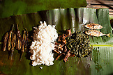 PHILIPPINES, Palawan, Barangay region, chicken, fish rice and vegetables are served family style on a banana leaf in Kalakwasan Village