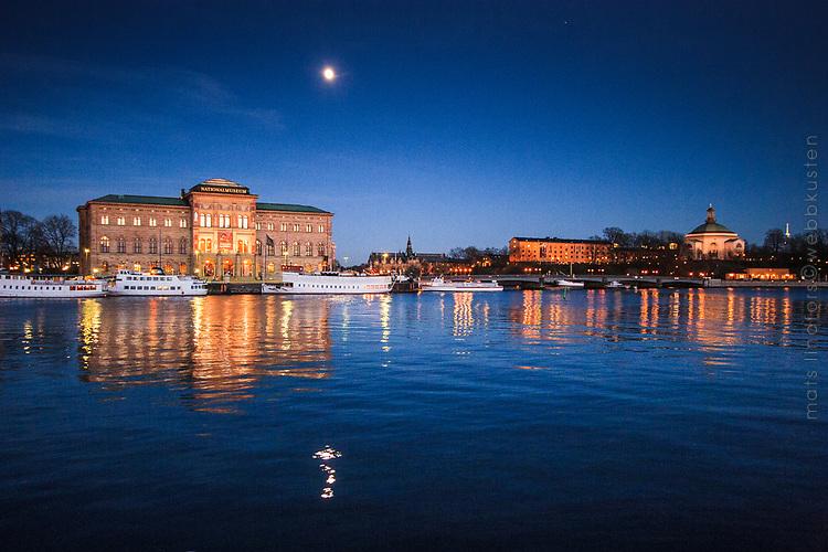 Fullmåne över Nationalmuseum i Stockholm med spegling i Strömmen