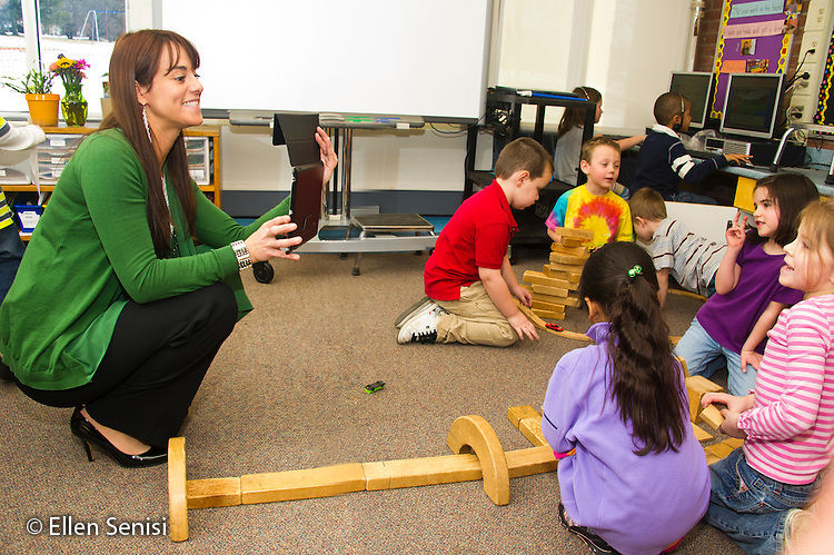 MR / Schenectady, NY. Zoller Elementary School (urban public school). Kindergarten inclusion classroom. Teacher uses digital camera in iPad (tablet computer) to photograph her students at play. Students have separated themselves into gender segragated peer groups. The teacher uses photos as an assessment tool and to document their activities and growth throughout the year. MR: War15. ID: AM-gKw. © Ellen B. Senisi.