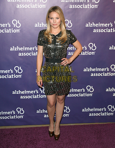 "KRISTEN BELL.at The 19th Annual ""A Night at Sardi's"" benefitting the Alzheimer's Association held at The Beverly Hilton Hotel in Beverly Hills, California, USA,.March 16th 2011..full length black gold dress shiny shoes metal embellished zip up  hand on hip                                                                                .CAP/RKE/DVS.©DVS/RockinExposures/Capital Pictures."