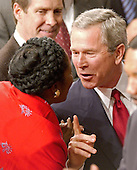 United States President George W. Bush shares a thought with United States Representative Sheila Jackson Lee (Democrat from the 18th District of Texas) as he departs the United States House of Representatives chamber following his State of the Union Address to a Joint Session of Congress in the Capitol in Washington, D.C. on February 2, 2005.  United States Senate Majority Leader Bill Frist (Republican of Tennessee) looks on with a smile at upper left.