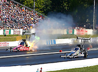 Jun. 1, 2014; Englishtown, NJ, USA; NHRA top fuel driver Spencer Massey (left) has an engine fire alongside Brittany Force during the Summernationals at Raceway Park. Mandatory Credit: Mark J. Rebilas-