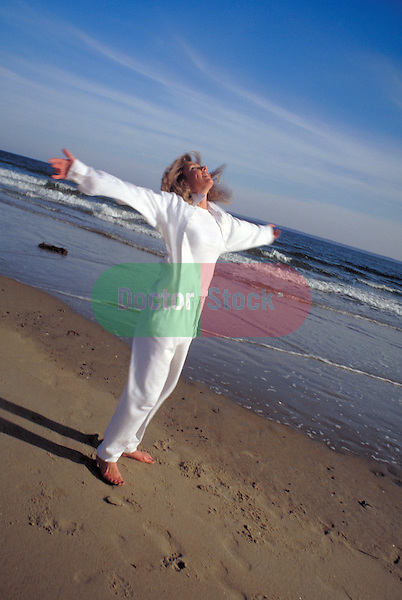 woman jumping and stretching at beach