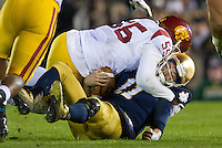 Irish quarterback Tommy Rees (11) is sacked by USC Trojans linebacker Lamar Dawson (55) in the third quarter at Notre Dame Stadium. Rees left the game after being injured on the play.