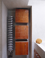 A coiled chrome radiator beside three identical cupboards in this contemporary bathroom