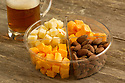 Snack tray with almonds, cheese and mug of beer