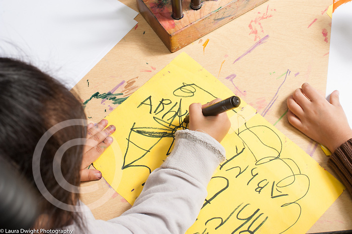 Education prechool overhead view of two children drawing with markers, one writing alphabet letters