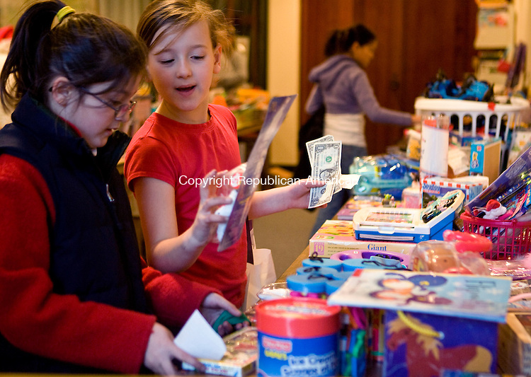 MIDDLEBURY, CT - 05 DECEMBER 2008 -120508JT03-<br /> Siobhan Flanagan, 8, shows Shannon Seman, also 8, an item for sale at Middlebury Public Library's annual Holiday Sale for children on Friday as the two shop for friends and family. The event also provided helpers and gift wrapping for shoppers. Simultaneously at the library was a bake sale and a silent auction.<br /> Josalee Thrift / Republican-American