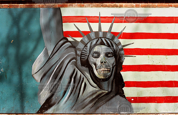 An Anti-American mural outside the former US embassy, depicting the Statue of Liberty with the face of a skull, standing in front of the red stripes of the American flag..