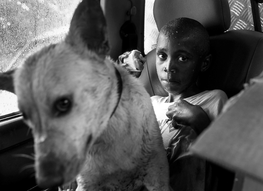 A boy and his dog take refuge from the rain in a CLAW vehicle after his dog was treated at a mobile CLAW clinic in Snake Park, South Africa. IFAW's CLAW program provides veterinary services to cats and dogs in some of the poorest shantytowns outside of Johannesburg, South Africa. 2/27/12 Julia Cumes/IFAW