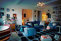 A retro styled living room with a blue sofa and two armchairs placed around a coffee table. The crowded room also has a dining table and chairs with striped upholstery and geometric and stirped pattern rugs. An open door gives a view to a bedroom beyond.