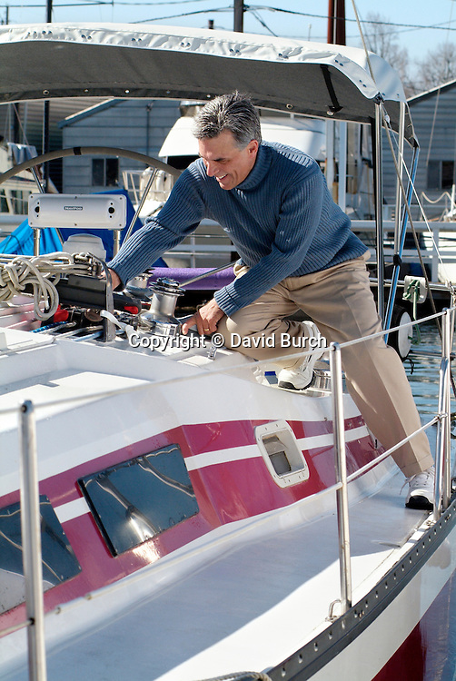 Man working rigging  on sailboat in marina
