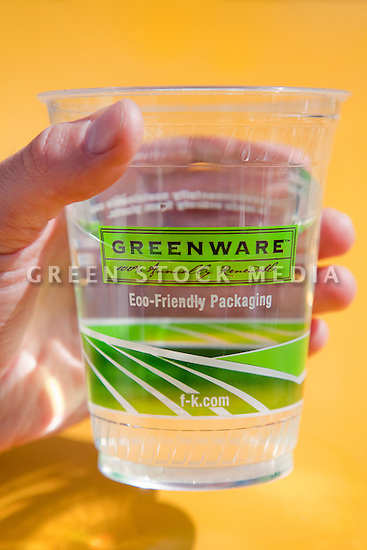 Close-up of person holding a Fabri-Kal's Greenware cold drink cup full of water. Made in American from NatureWorks Ingeo biopolymer, a resin derived entirely from plants. The cups are used for drinking water for customers at the outside tables of the Coast Cafe in Bolinas, California, USA