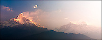 Machapuchare, aka Fishtail, is basking in the early morning sunlight. Annapurna mountains on the right in fog.