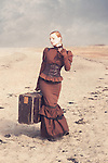 Young woman in a victorian dress holding an old suitcase alone outdoors beside the sea