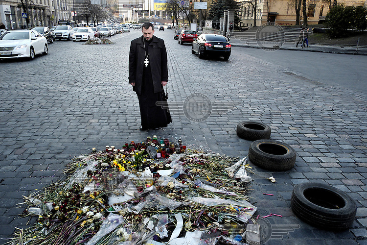 An Orthodox priest prays in front of a memorial of flowers to those killed in clashes with police on Hrushchevskoho. Protests against the government of President Viktor Yanukovych were sparked on 21 November 2013 by the Ukrainian government's decision to suspend preparations for the signing of an association agreement with the European Union that would have increased trade with the EU. Some believe that the U-turn came about as a result of pressure from President Putin of Russia who wants Ukraine to join a customs union with itself, Kazakhstan and Belarus. Russia offered 15 billion dollars of soft loans and reduced price gas to Ukraine at the same time as discussions with the EU were taking place. After weeks of protests and a number of deaths, Prime Minister Mykola Azarov and the entire cabinet resigned. On 18 February, after Yanukovych's party scuppered a move to change the constitution to reduce the powers of the president, renewed fighting between protesters and police broke out and had cost the lives of around 80 people by Friday 21st February. By 22 February Yanukovych had fled Kiev. In the days following the Ukrainian parliament decided to strip him of the presidency.