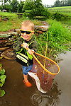 In the summer a young boy has a fish in a net by a pond wearing a raincoat  in northeast PA