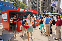 Foodies pick up their pre-ordered picnic lunches for Seamless Picnic Day at the Seamless stand at Flatiron Plaza in New York on Wednesday, July 29, 2015. The first 200 people who ordered got a lobster roll, sides and a Seamless branded picnic blanket at the giveaway deal of $12. Seamless merged with GrubHub delivery service and had its IPO last year. (© Richard B. Levine)