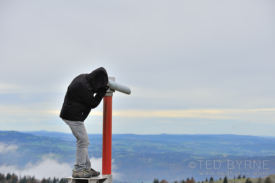 A child looks through a telescope from a hillside to the distance