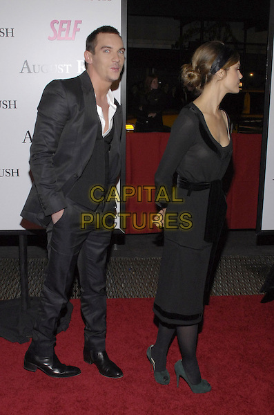 "JONATHAN RHYS MEYERS & KERI RUSSELL.The New York premiere of Warne Bros. Pictures' ""August Rush"" held at  the Ziegfeld Theater, New York, New York, USA..November 11th, 2007.full length black headband dress belt sash green shoes profile suit hands in pockets myers funny bun.CAP/ADM/BL.©Bill Lyons/AdMedia/Capital Pictures. *** Local Caption ***"
