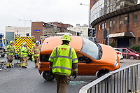 Pictured: Emergency service attend the scene where an orange Fiat Panda toppled over in Cardiff, Wales, UK. Thursday 27 )ctober 2016<br />